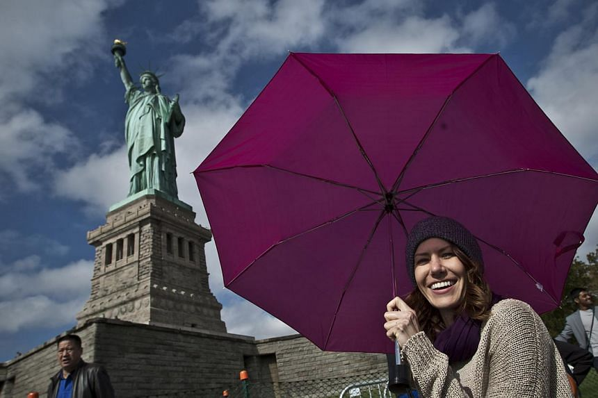 Tourists pose for pictures during a visit to the Statue of Liberty on Oct 13, 2013 in New York City. -- PHOTO: AFP