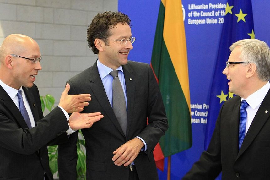 Lithuanian Finance Minister Rimantas Sadzius (R) welcomes Joerg Asmussen (L), member of the executive board of the European Central Bank (ECB), and Jeroen Dijsselbloem (C), Dutch Finance Minister and president of the Board of Governors of the Europea