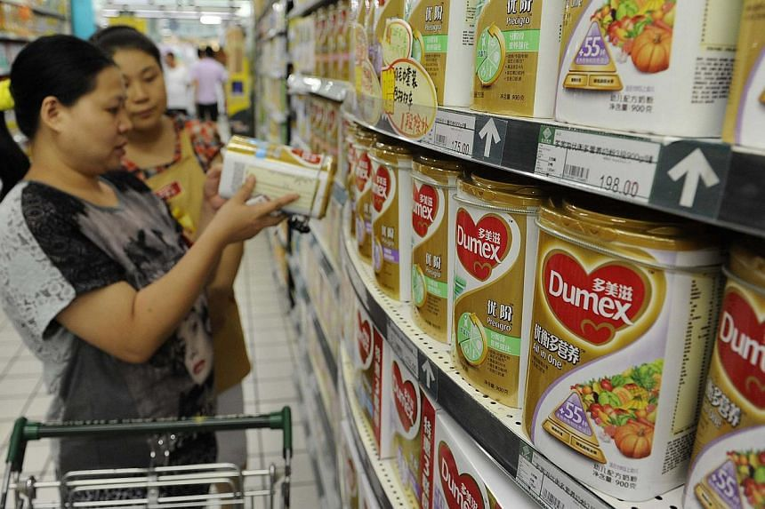 A sales assistant (back) helps a customer to select Dumex milk powder at a supermarket in Hefei, Anhui province in this Aug 5, 2013.French food maker Danone S.A. said it will appoint new management at its Dumex infant milk powder operation in C