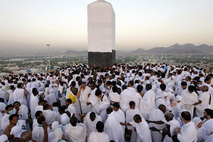 Muslim pilgrims pray on a rocky hill called the Mountain of Mercy, near the holy city of Mecca, Saudi Arabia, Monday, Oct. 14, 2013.Throngs of Muslim pilgrims converged on Monday on Muzdalifah to prepare for Eid al-Adha feast after a day of pra