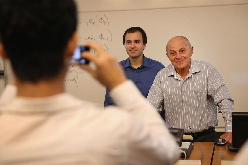 University of Chicago professor Eugene Fama poses for a picture with a student after teaching a class at the university on October 14, 2013 in Chicago, Illinois. Winning a Nobel prize was no excuse for cancelling class for two economics professors wh