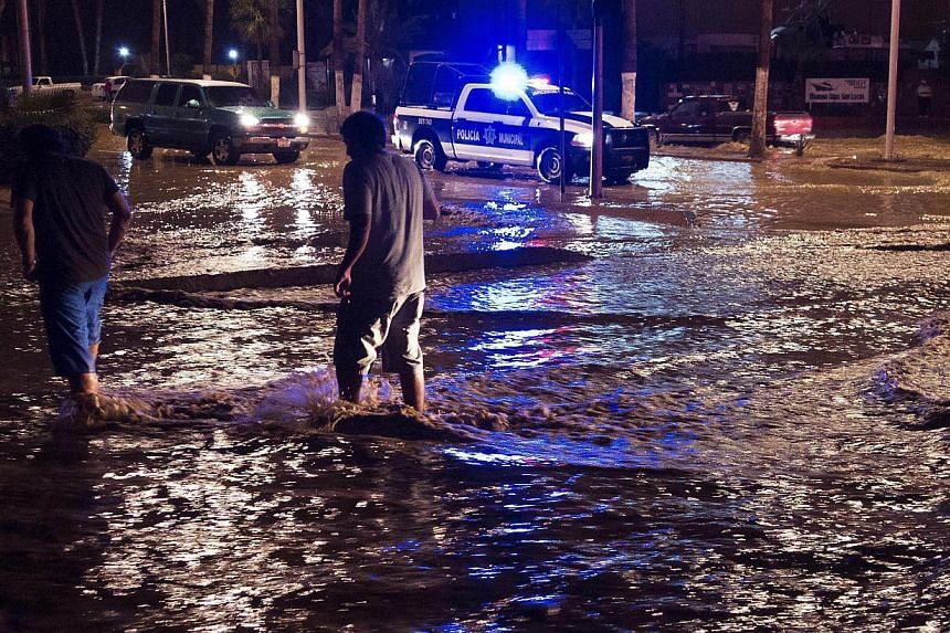 People traverse flood waters in the streets of Cabo San Lucas, Mexico, in the early hours of the day on Monday, Oct 14, 2013, as heavy rain turns the streets into small rivers.Tropical Storm Octave pummelling Mexico's Baja California peninsula