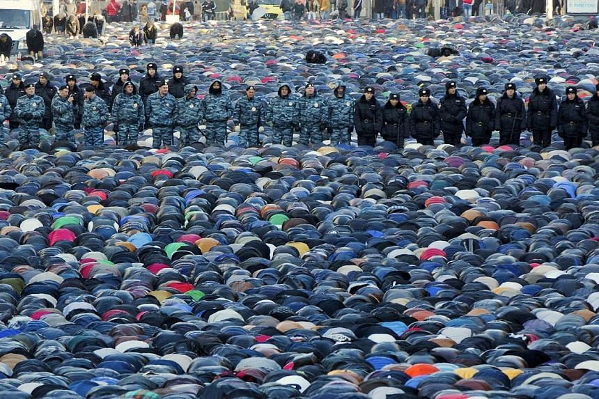 Russian police officers stand guard as Muslims pray outside the main Moscow mosque during celebrations of Eid al-Adha on Tuesday, Oct 15, 2013. Police stepped up security in Moscow on Tuesday to prevent a repeat of rioting over the killing of an