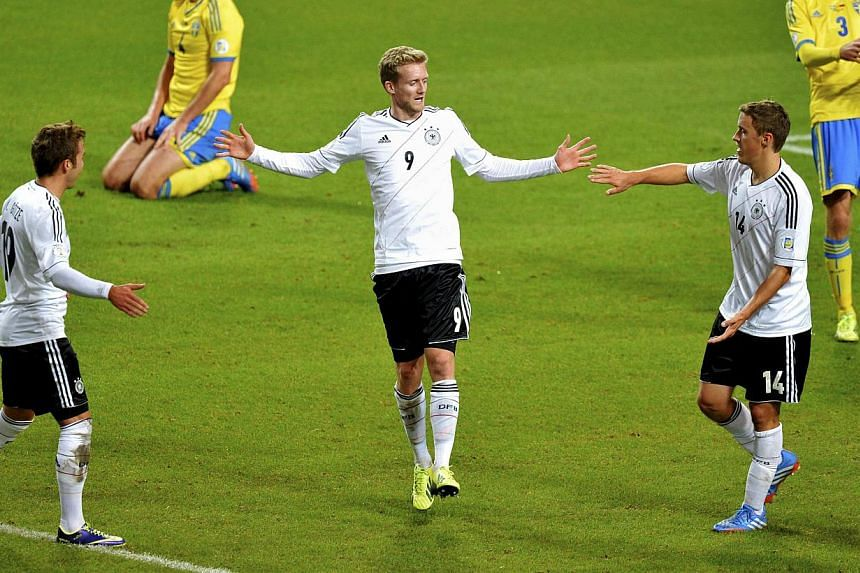 Germany's Andre Schuerrle (centre) celebrates his goal against Sweden with teammates Mario Goetze (left) and Max Kruse while Sweden's Per Nilsson (2nd left) and Mikael Antonsson react during their 2014 World Cup qualifying soccer match at Friends Are
