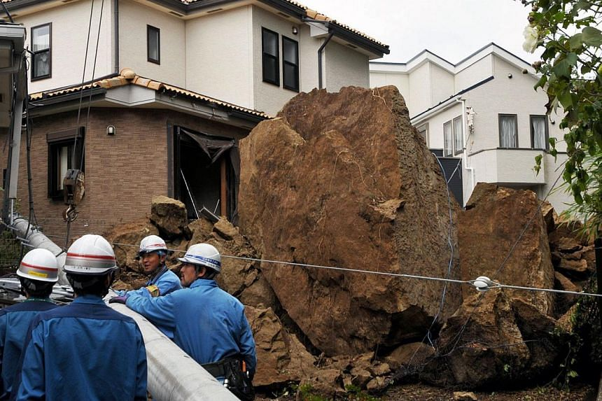"A house and an electric pole smashed by large rocks from a collapsed slope caused by heavy rain in Kamakura, suburban Tokyo on Oct 16, 2013. At least three people died as Typhoon Wipha - the ""strongest in 10 years"" - passed close to Tokyo, causing la"