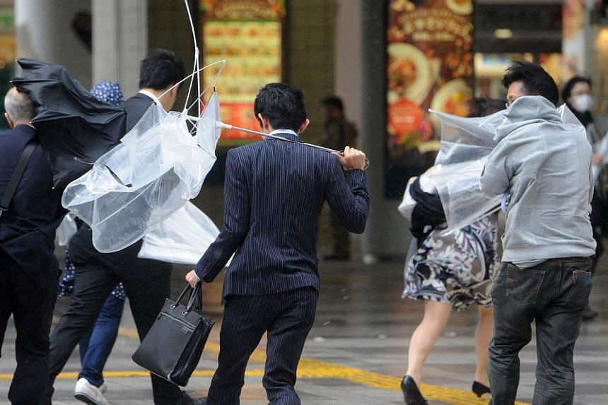 "People walk against strong wind and rain in Tokyo on Oct 16, 2013. At least three people died as Typhoon Wipha - the ""strongest in 10 years"" - passed close to Tokyo, causing landslides that swallowed houses on a Japanese island on Wednesday. -- PHOTO"