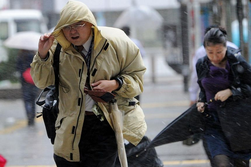 """People walk against strong wind and rain in Tokyo on Oct 16, 2013. At least three people died as Typhoon Wipha - the """"strongest in 10 years"""" - passed close to Tokyo, causing landslides that swallowed houses on a Japanese island on Wednesday.--"""