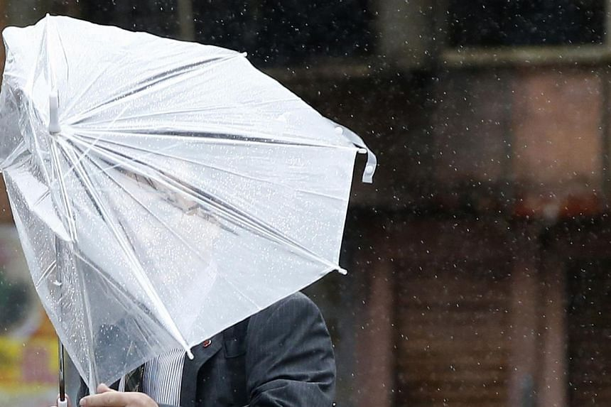 A man struggles against strong wind and rain caused by approaching Typhoon Wipha at a business district in Tokyo on Wednesday, Oct 16, 2013. -- PHOTO: REUTERS