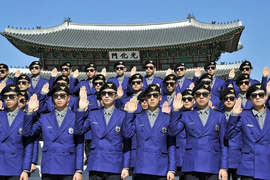 """South Korea unveiled its new """"tourist police"""" force at Gwanghwamun square in Seoul on Oct 16, 2013, with snappy uniforms from rapper Psy's costume designer and a Gangnam Style launch. The tourist police will protect tourists from being ripped off dur"""