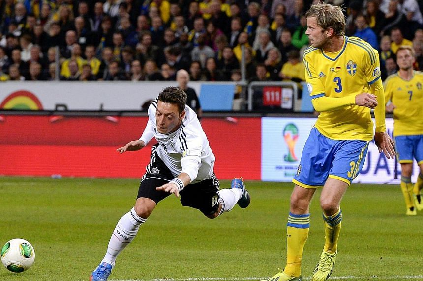 Germany's midfielder Mesut Oezil (left) and Sweden's defender Mikael Antonsson vie for the ball during the Fifa 2014 World Cup group C qualifying football match Sweden vs Germany in Solna, Sweden, on Oct 15, 2013. Germany beat Sweden 5-3. -- PHOTO: A