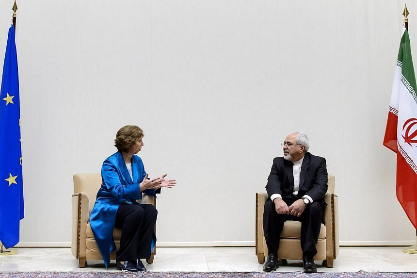 European Union foreign policy chief Catherine Ashton (L) speaks with Iranian Foreign Minister Mohammad Javad Zarif during a photo opportunity before the start of two days of closed-door nuclear talks at the United Nations offices in Geneva Oct 15, 20