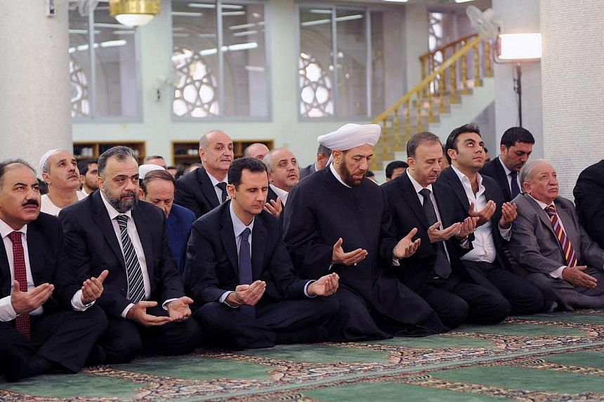 Syrian President Bashar Assad (third left) prays on the first day of Eid al-Adha at the Sayeda Hassiba mosque in Damascus, Syria, on Oct 15, 2013, in this photo released by the Syrian official news agency Sana. -- PHOTO: AP