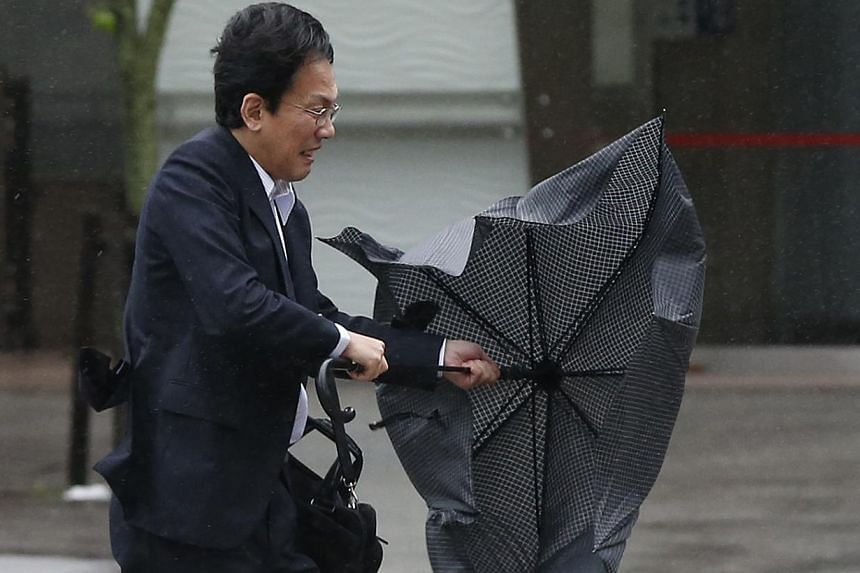 "A man struggles against strong wind and rain caused by approaching Typhoon Wipha at a business district in Tokyo on Oct 16, 2013. At least three people died as Typhoon Wipha - the ""strongest in 10 years"" - passed close to Tokyo, causing landslides th"