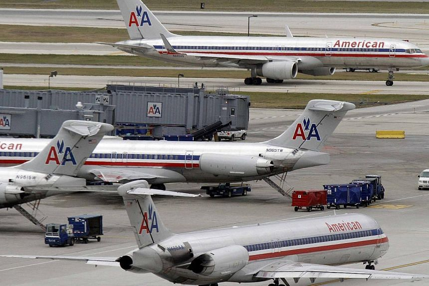 American Airlines planes sit at their gates while others taxi for arrival and departure at O'Hare International airport in Chicago in this Nov 29, 2011 file photo.American Airlines said on Wednesday it plans to add nonstop flights to Hong Kong
