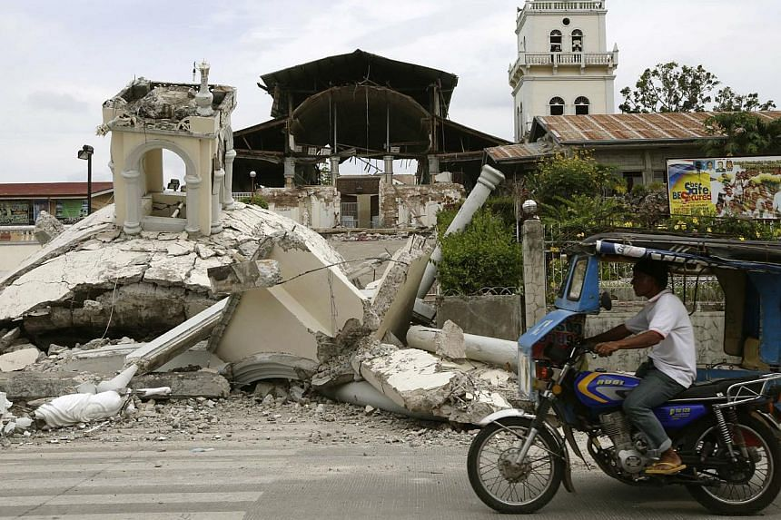 A man drives his tricycle past the quake-damaged San Isidro de Labrador church in Tubigon township, Bohol province in central Philippines on October 16, 2013. The 7.2-magnitude quake which hit Bohol and Cebu provinces on October 15, 2013, damaged chu