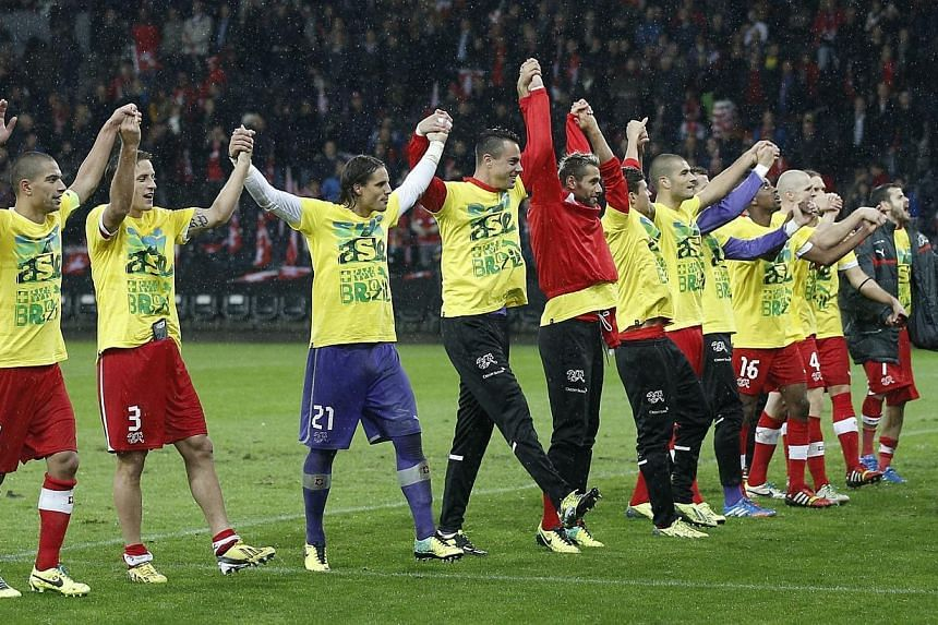 Switzerland's players celebrate after qualifying for FIFA World Cup 2014 at the Stade de Suisse stadium in Bern, Switzerland on Tuesday, Oct 15, 2013. Switzerland will be among the eight seeded teams at the World Cup draw in December after
