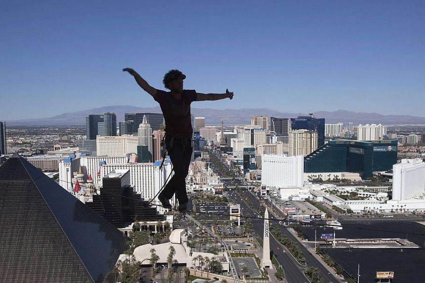 Daredevil slackline athlete Andy Lewis sets the world record for the longest urban highline walk at 110m long outside the 63rd floor of Mandalay Bay Resort in Las Vegas, Nevada on Oct 16, 2013. -- PHOTO: REUTERS