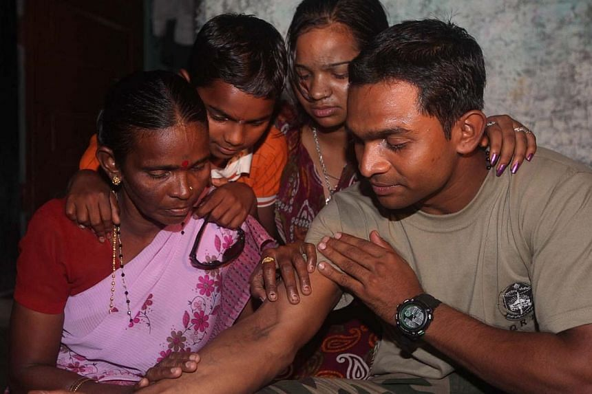 Indian police commando, Ganesh Raghunath Dhangade (right), shows a tatoo to his family in Thane district on the outskirts of Mumbai on Oct 16, 2013.Mr Dhangade,who got lost as a child at a crowded railway station, was reunited with his fa