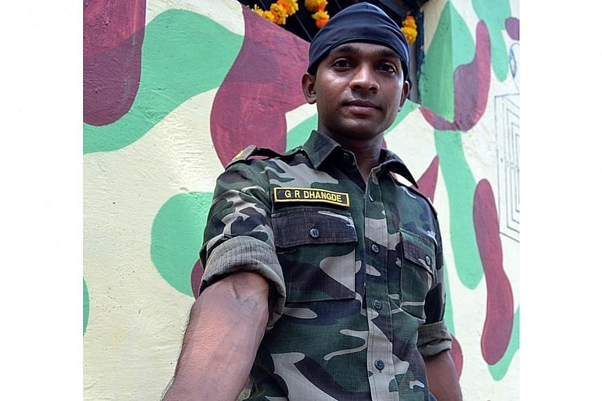 Indian police commando, Ganesh Raghunath Dhangade, shows his tattoo in Thane district on the outskirts of Mumbai on Oct 16, 2013.Mr Dhangade,who got lost as a child at a crowded railway station, was reunited with his family after 24 years