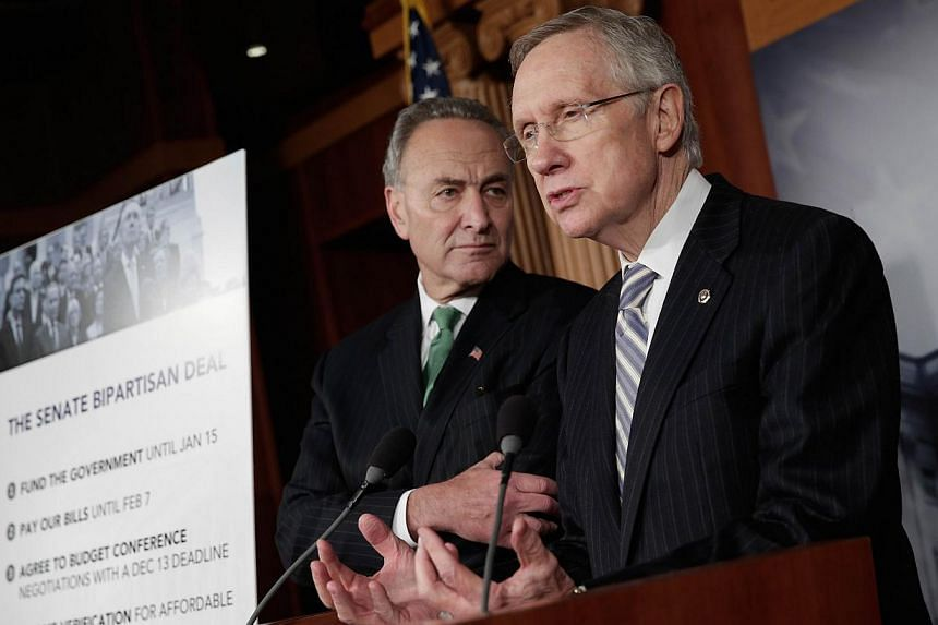 United States Senate Majority Leader Harry Reid, a Democrat from Nevada, speaks to the media as Senator Charles Schumer (left), a Democrat from New York, looks on after reaching an agreement to end the government shutdown at the US Capitol in Washing