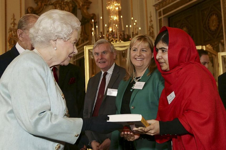 Malala Yousafzai gives a copy of her book I am Malala, to Britain's Queen Elizabeth during a Reception for youth, education and the Commonwealth at Buckingham Palace, in London, Friday, Oct 18, 2013. Malala was reduced to fits of laughter on Friday,