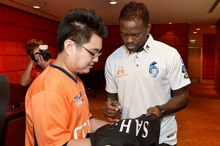 Louis Saha, seen here signing a shirt for Man U fan Jason Quek, says while David Moyes wanted strikers during his reign at Everton to defend too, he should let Robin van Persie and Wayne Rooney to express their flair.