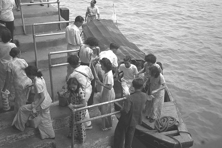 1950: A bird's eye view of Kusu Island pilgrims (above) returning from their annual trip, which takes place in the ninth lunar month. The number of pilgrims has been falling, with 47,000 people making the journey last year, compared with 77,000 in 20