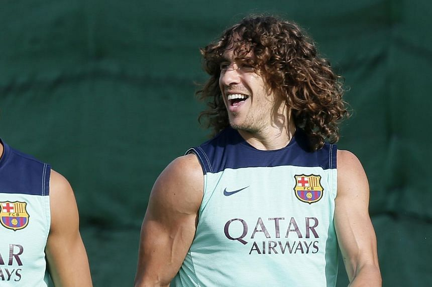 Barcelona captain Carles Puyol smiles to his teammates during a training session at the Sport Centre FC Barcelona Joan Gamper on Friday, Oct 18, 2013. Puyol has been cleared to make his return to action in a Spanish Primera Liga match again