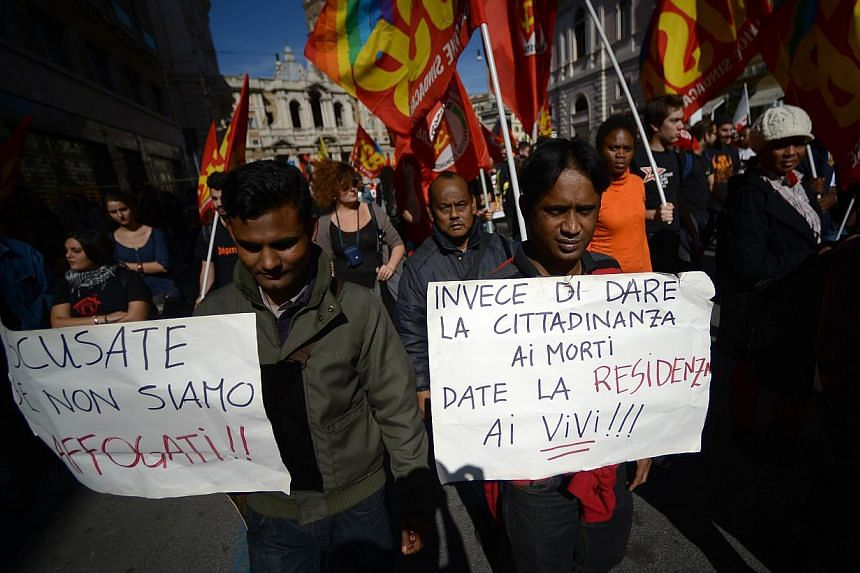 "Immigrants hold placards reading ""Instead of giving citizenship to the dead, give it to the living!!"" (right) and ""Sorry if we are not drowned!!"" on Friday, Oct 18, 2013, in Rome during a demonstration of Italian trade union Cobas against austerity m"