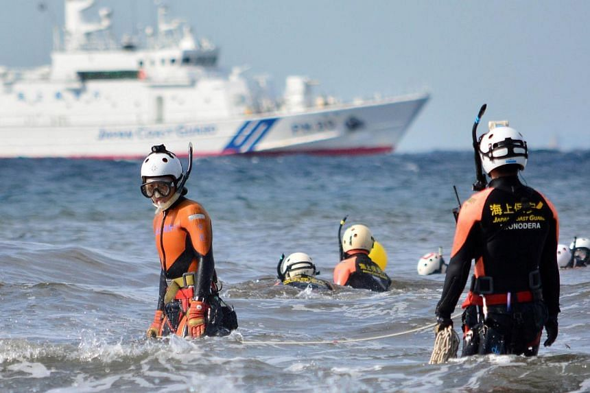 A Japanese Coast Guard marine rescue unit enters the sea to search for missing persons at Oshima island, 120km south of Tokyo on Oct 18, 2013. Frogmen were on Friday scouring waters off the coast of a Japanese island where landslides buried houses wh