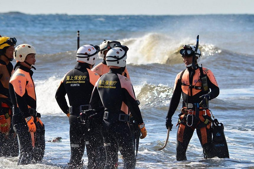A Japanese Coast Guard marine rescue unit talk before searching for missing persons off Oshima island, 120km south of Tokyo on Oct 18, 2013. Frogmen were on Friday scouring waters off the coast of a Japanese island where landslides buried houses when