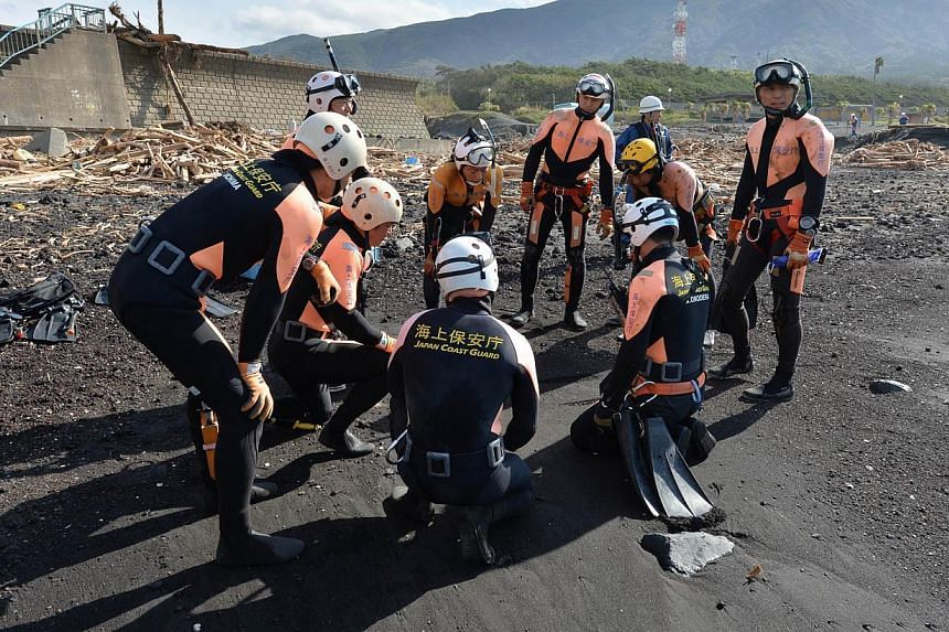 A Japanese Coast Guard marine rescue unit hold a meeting before an operation to seek typhoon victims, on the beach at Oshima island, 120km south of Tokyo on Oct 18, 2013. Frogmen were on Friday scouring waters off the coast of a Japanese island where