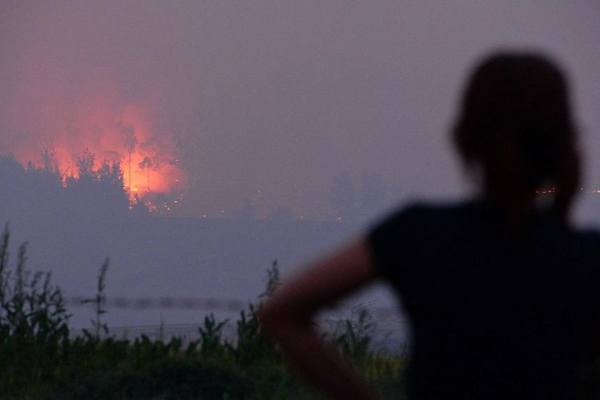 A resident looks at the flames from a bush fire that erupted in Sydney's western suburb of Castlereagh, New South Wales on Sept 10, 2013. -- PHOTO: AFP