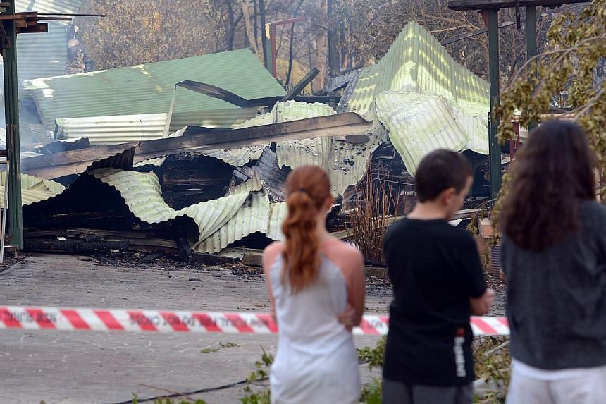 Children look at a house burnt out by bushfires in Winmalee in Sydney's Blue Mountains on Oct 18, 2013. -- PHOTO: AFP