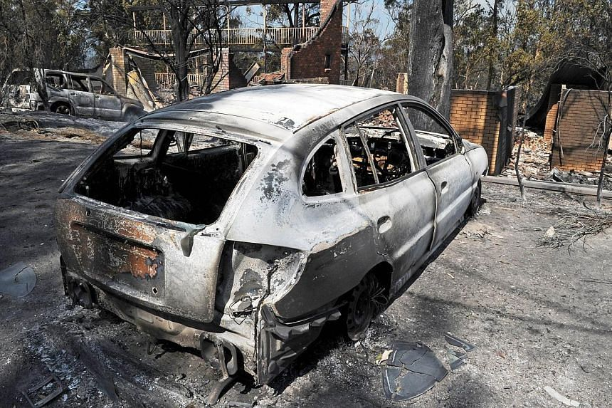 A burnt out car sits in front of a house destroyed by bushfires in Winmalee in Sydney's Blue Mountains on Oct 18, 2013. -- PHOTO: AFP 29654607