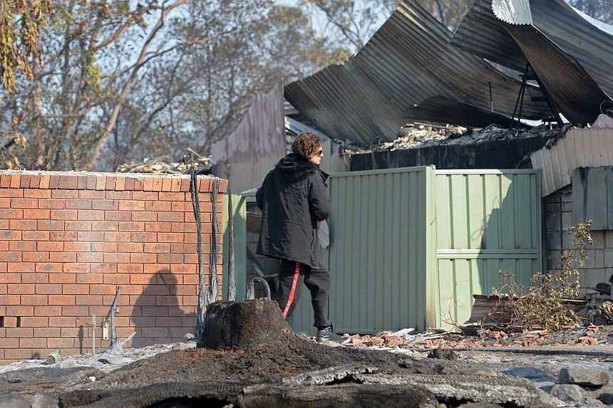 A man (centre) walks near houses destroyed by bushfires at Winmalee in Sydney's Blue Mountains on Oct 18, 2013. -- PHOTO: AFP