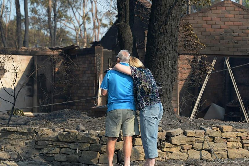 A couple look at a house burnt out by bushfires in Winmalee in Sydney's Blue Mountains on Oct 18, 2013. -- PHOTO: AFP