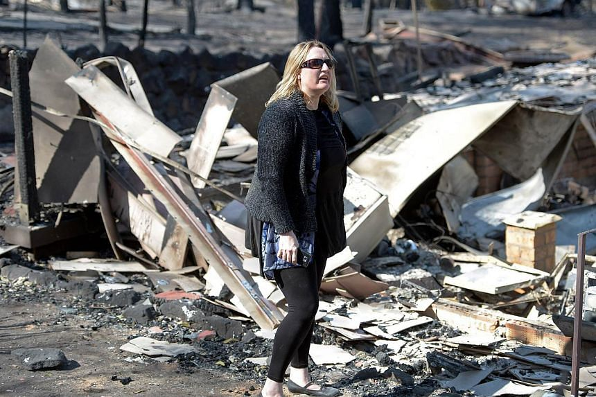 Resident Catherine Hubbard (centre) stands in the burnt out ruins of her house destroyed by bushfires in Winmalee in Sydney's Blue Mountains on Oct 18, 2013. -- PHOTO: AFP