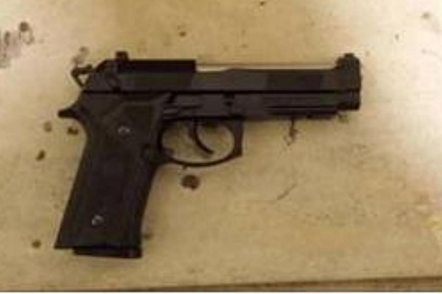 A 30-year-old Singaporean was charged in court on Saturday with unlawful possession of a black 'Bereta' air pistol under the Arms Offences Act. -- PHOTO: SINGAPORE POLICE FORCE