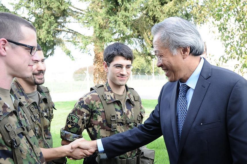 Defence Minister Ng Eng Hen (right) meeting with Swiss reservists on their annual refresher training. -- PHOTO: MINDEF
