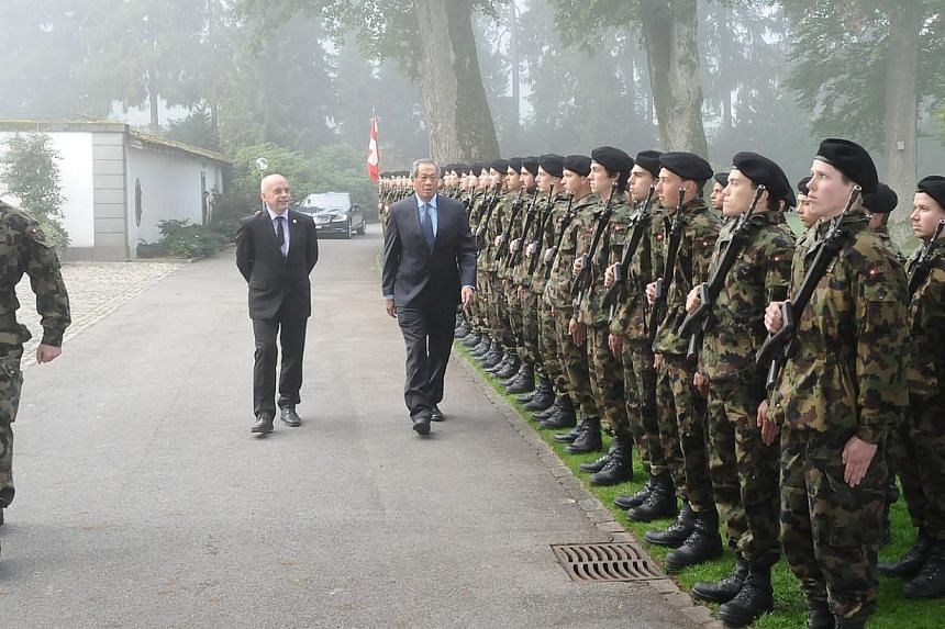 Defence Minister Ng Eng Hen (centre) inspecting the military honours at the Lohn Manor House. -- PHOTO: MINDEF