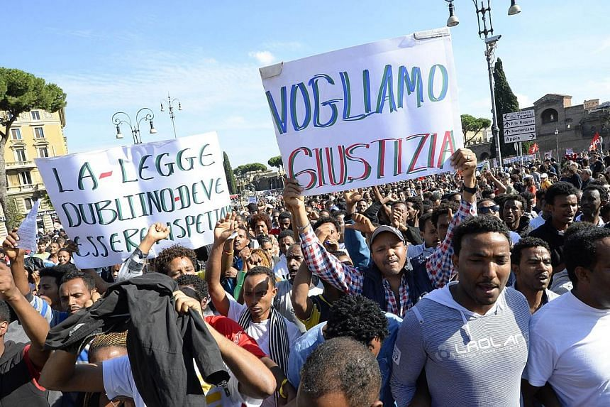 A group of migrants takes part in an anti-austerity protest led by anti high-speed rail movement (No Tav) and an association for rights to housing, on Oct 19, 2013. Thousands of people took to the streets of Rome on Saturday for an anti-austerity pro