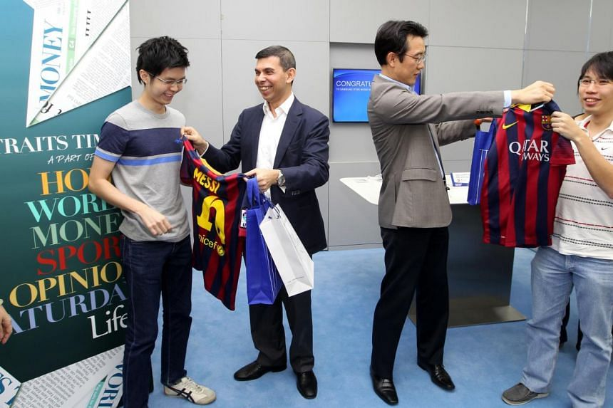 Mr Ng (far left) receiving his prizes last night from ST editor Mr Fernandez, while Samsung's Mr Lee presents Mr Sng (far right) with his prizes. The winners will fly to Spain to watch Barcelona play Real Madrid.