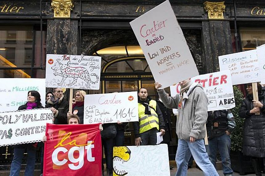 Employees of the French luxury jeweller Cartier demonstrate to protest against low incomes in front of the main shop near Vendome place in Paris, on Oct 18, 2013. -- FILE PHOTO: AFP