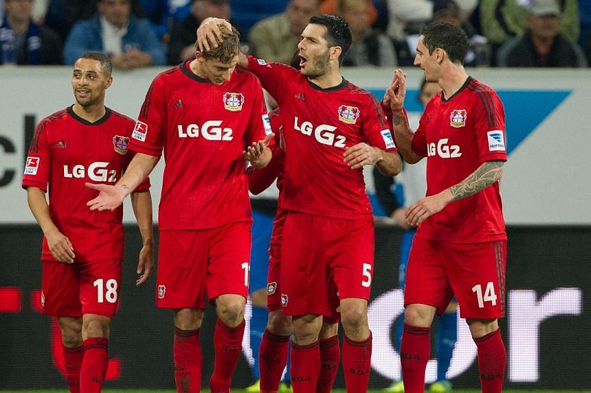 Bayer Leverkusen's Stefan Kiessling (second from left) is congratulated by teammates (from left) Sidney Sam, Emir Spahic and Roberto Hilbert after the referee decided that he had scored Leverkusen's second goal against Hoffenheim on Saturday, Oct 19,