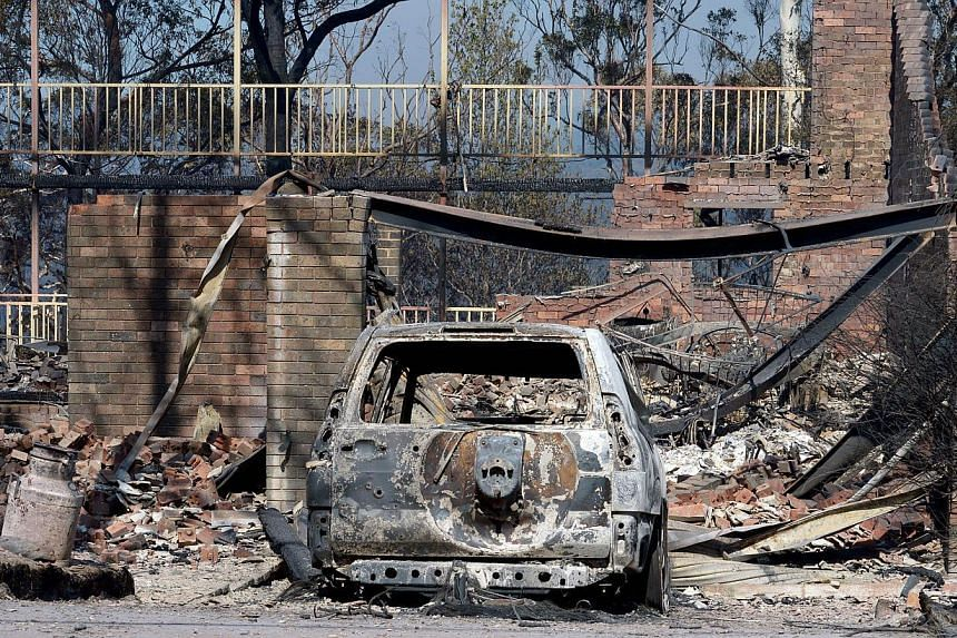 A burnt out car sits at the front of a house destroyed by bushfires in Winmalee in Sydney's Blue Mountains on Friday, Oct 18, 2013.Australian fire services warned on Sunday, Oct 20, 2013, that parts of New South Wales were facing the most dange