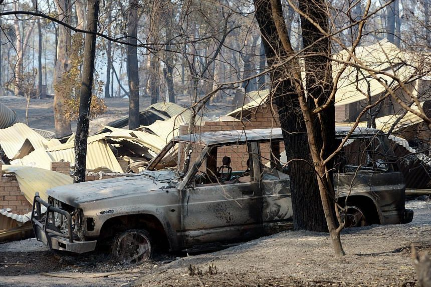A burnt out car sits at the front of a house destroyed by bushfires in Winmalee in Sydney's Blue Mountainson Friday, Oct 18, 2013. -- PHOTO: AFP