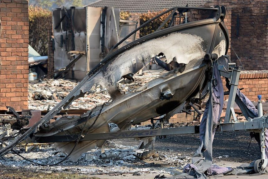 A burnt out boat sits in front of a house destroyed by bushfires in Winmalee in Sydney's Blue Mountainson Friday, Oct 18, 2013. -- PHOTO: AFP