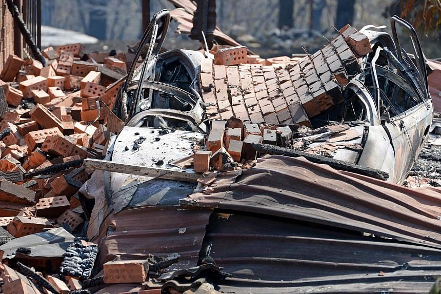 A car lies under bricks at the front of a house destroyed by bushfires at Winmalee in Sydney's Blue Mountainson Friday, Oct 18, 2013. -- PHOTO: AFP