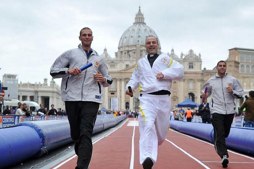 "Men take part in the ""100 Metres of Running and Faith"" event in front of St Peter's square on Sunday, Oct 20, 2013, at the Vatican. Catholic faithful sprinted along the main avenue leading to the Vatican on Sunday in an unusual initiative h"
